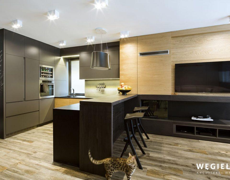 Kuchnia otwarta na salon w mieszkaniu, musi być zaprojektowana z dbałością o każdy detal, bo jest widoczna z różnych pomieszczeń. To założenie spełnił architekt.