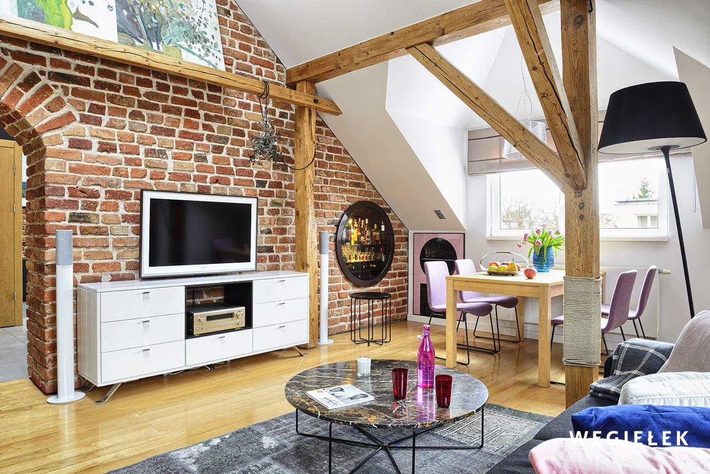 Czarna, stojąca lampa na tle białej ściany w pomieszczeniu z cegły z odkrytymi belkami z drewna, to odważne połączenie projektanta poddasza z Warszawy