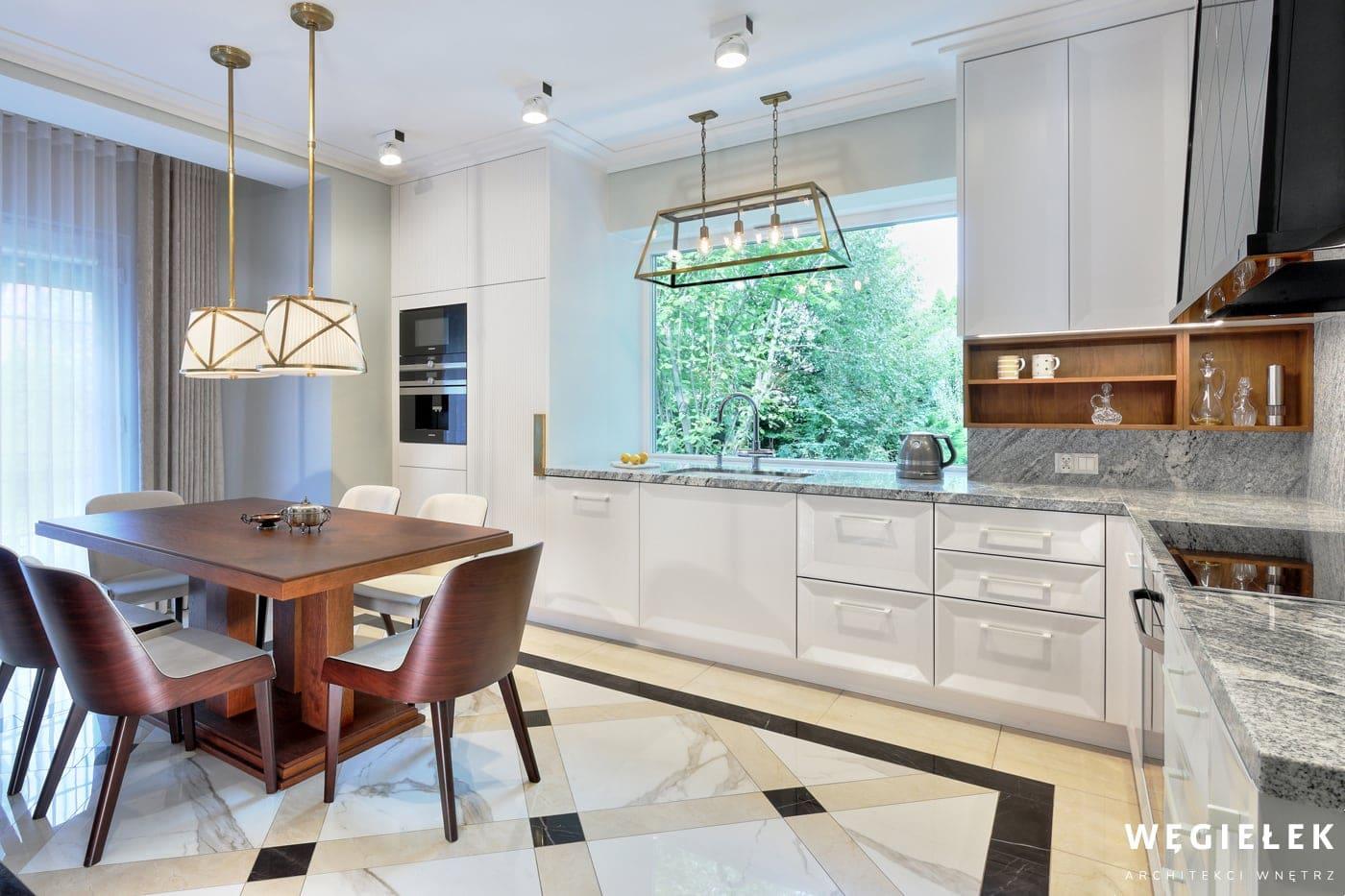 Projektant domów postawił na ciekawe rozwiązanie, połączył przeszłość z teraźniejszością, nowoczesne biele i szarości, tafle marmuru z kolorem drewna.