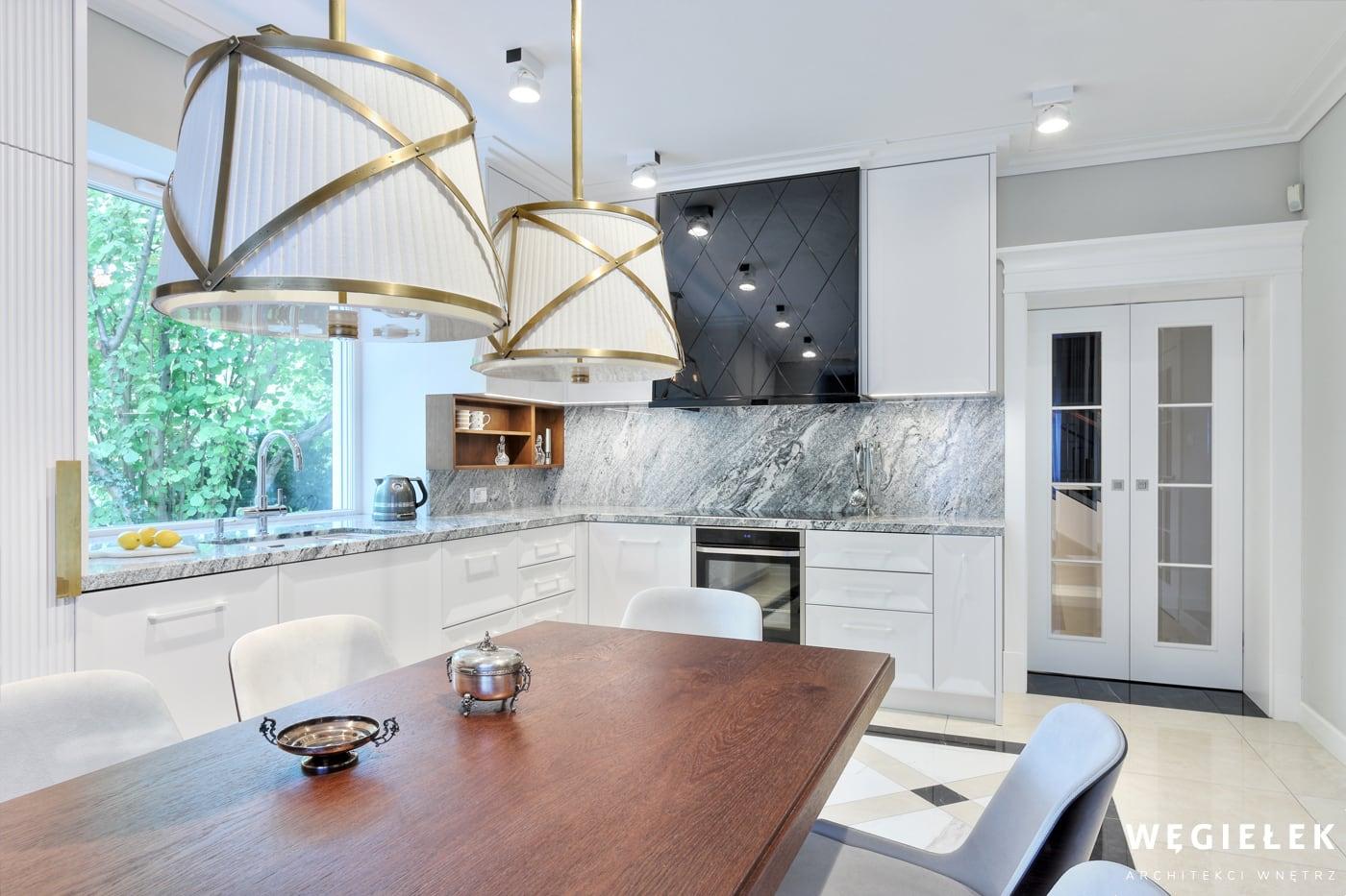 Kuchnia połączona z jadalnią stworzona przez projektanta domów, musi mieć dobrze oświetlone wnętrze. Można górne światła połączyć z dodatkowymi nad stołem.