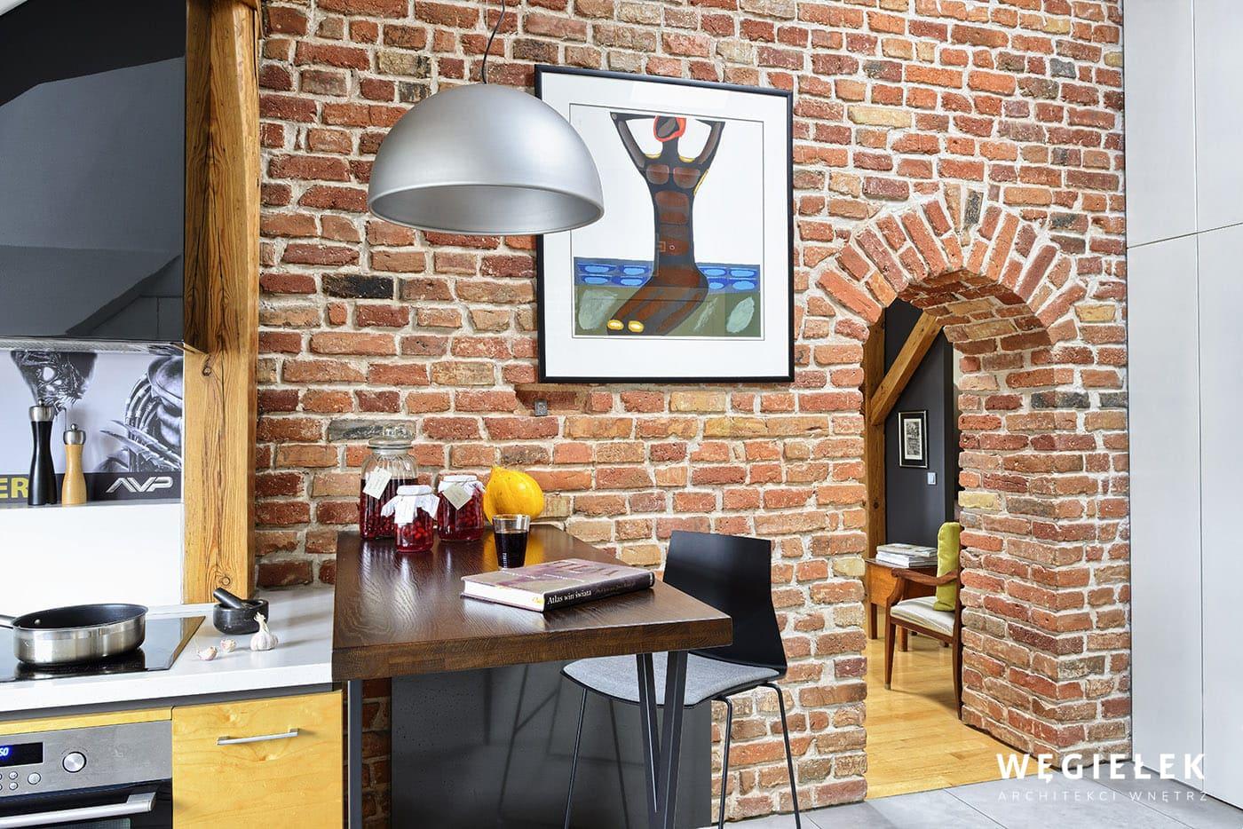 Stary fragment ściany z cegły jest uroczy ze względu na otwór drzwiowy o oryginalnym kształcie. Wykorzystał go projektant poddasza i pokazał w całej krasie.