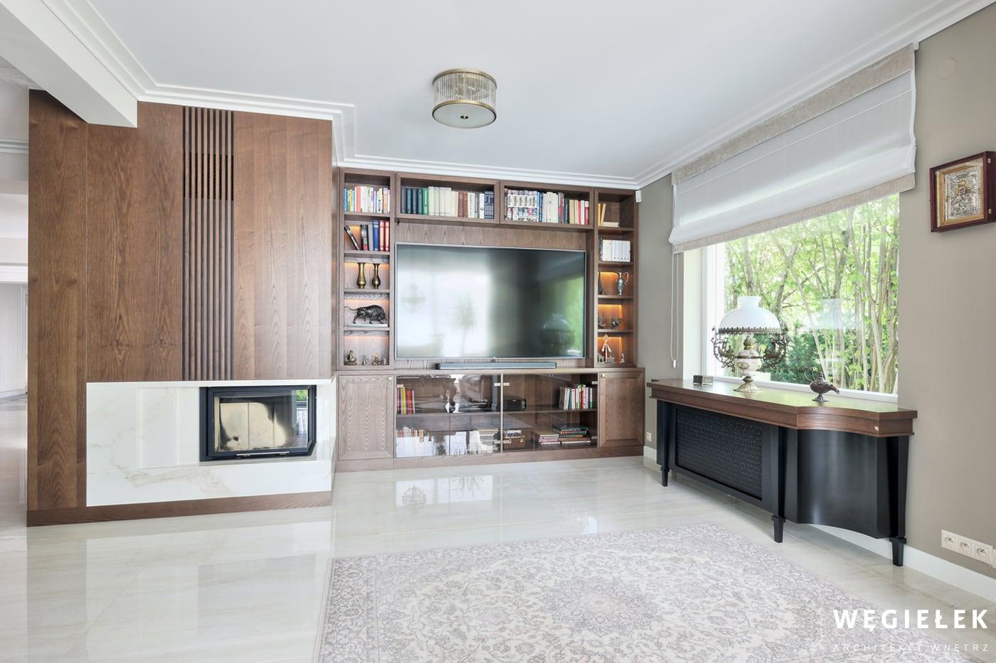 Salon w tej propozycji architekta domów to ciekawe wnętrze z jasną podłogą i ciemnymi, w kolorze drewna ścianami. Tradycyjny kominek współgra tu z telewizorem.