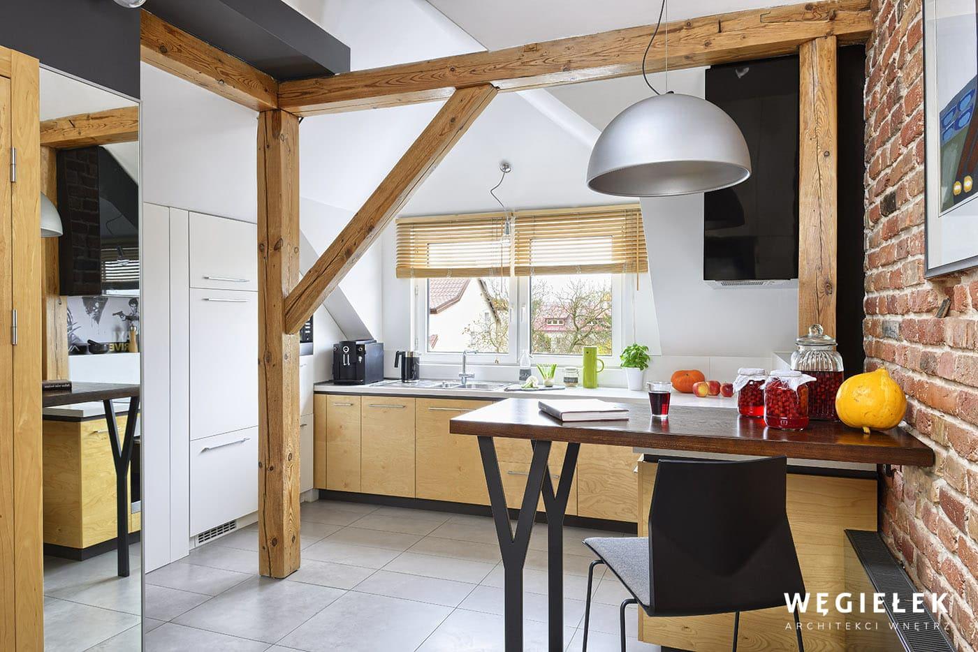 Drewniany blat barowy stanowi świetne uzupełnienie kuchni i wyznacza umowną granicę z salonem. Architekt wnętrz na tym poddaszu przymocował go do ściany.