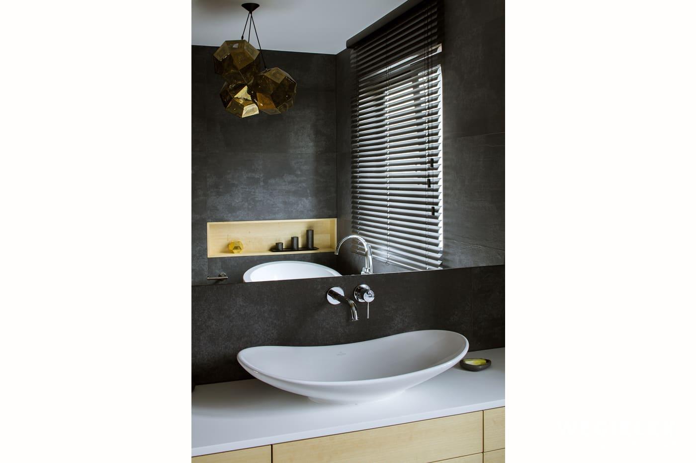 Zachwycający kształt białej umywalki wkomponowanej w drewnianą szafkę jest ciekawą koncepcją projektanta wnętrz mieszkań z Warszawy. Dodatki to lustro i lampa.