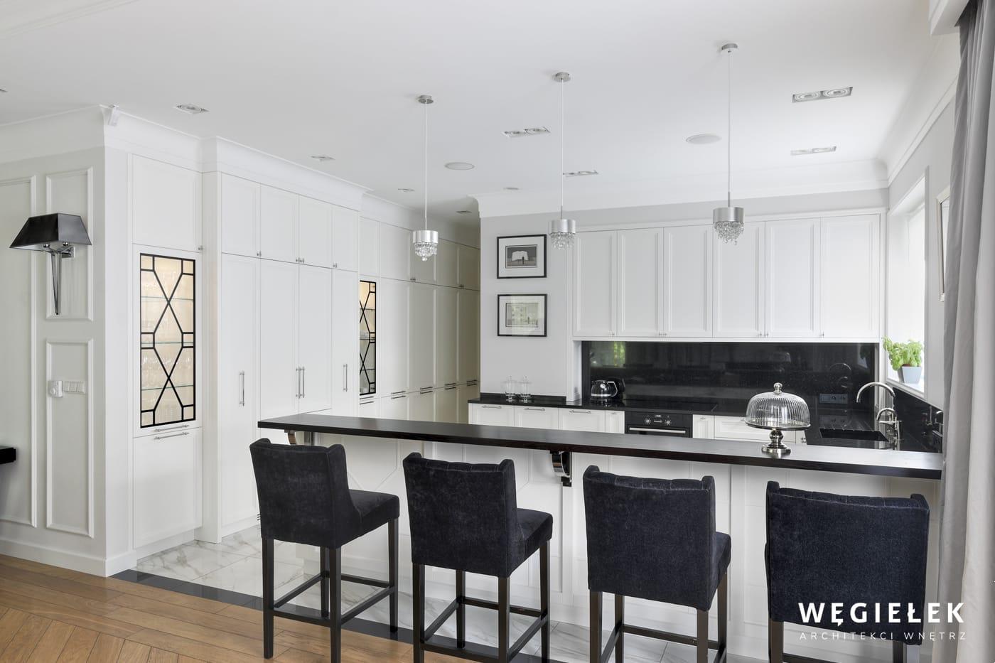 Architekt wnętrz sprawił, że odważna biel, barek i wysokie krzesła nakreśliły nowoczesny styl kuchni. Jest wrażenie czystości i indywidualnego wyglądu.