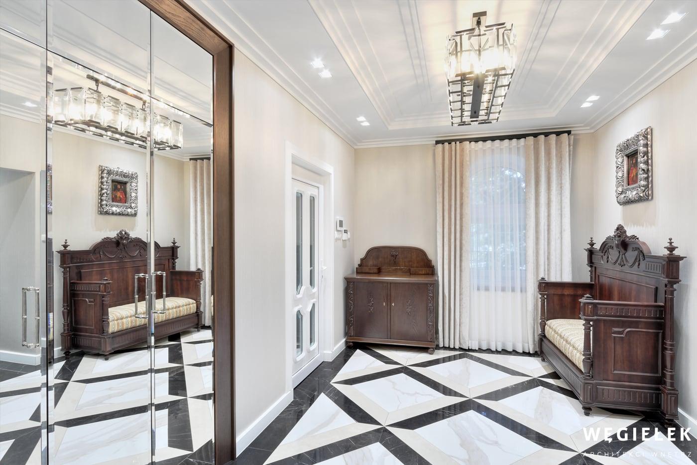 Klasyczny hol to miejsce, w którym możemy zostawić wierzchnie ubranie. Ten stworzony przez projektanta domów, zdobią przepiękne meble oraz lustrzana szafa.
