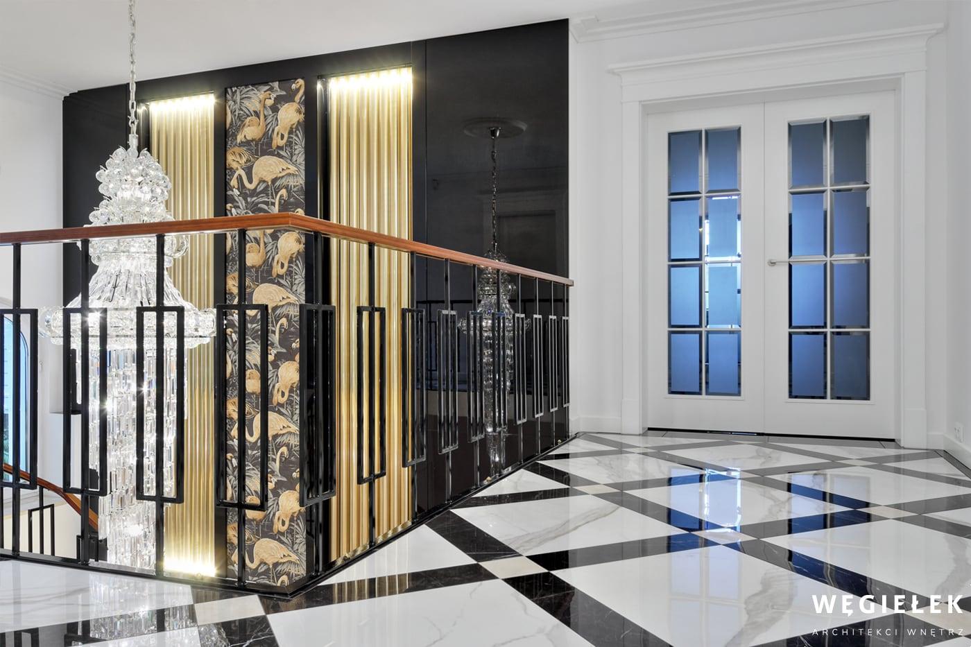 Wyrafinowany projekt architekta wnętrz domów tym razem dotyczy klatki schodowej. To odważne połączenie tapety w złote flamingi, marmurów i kryształów.