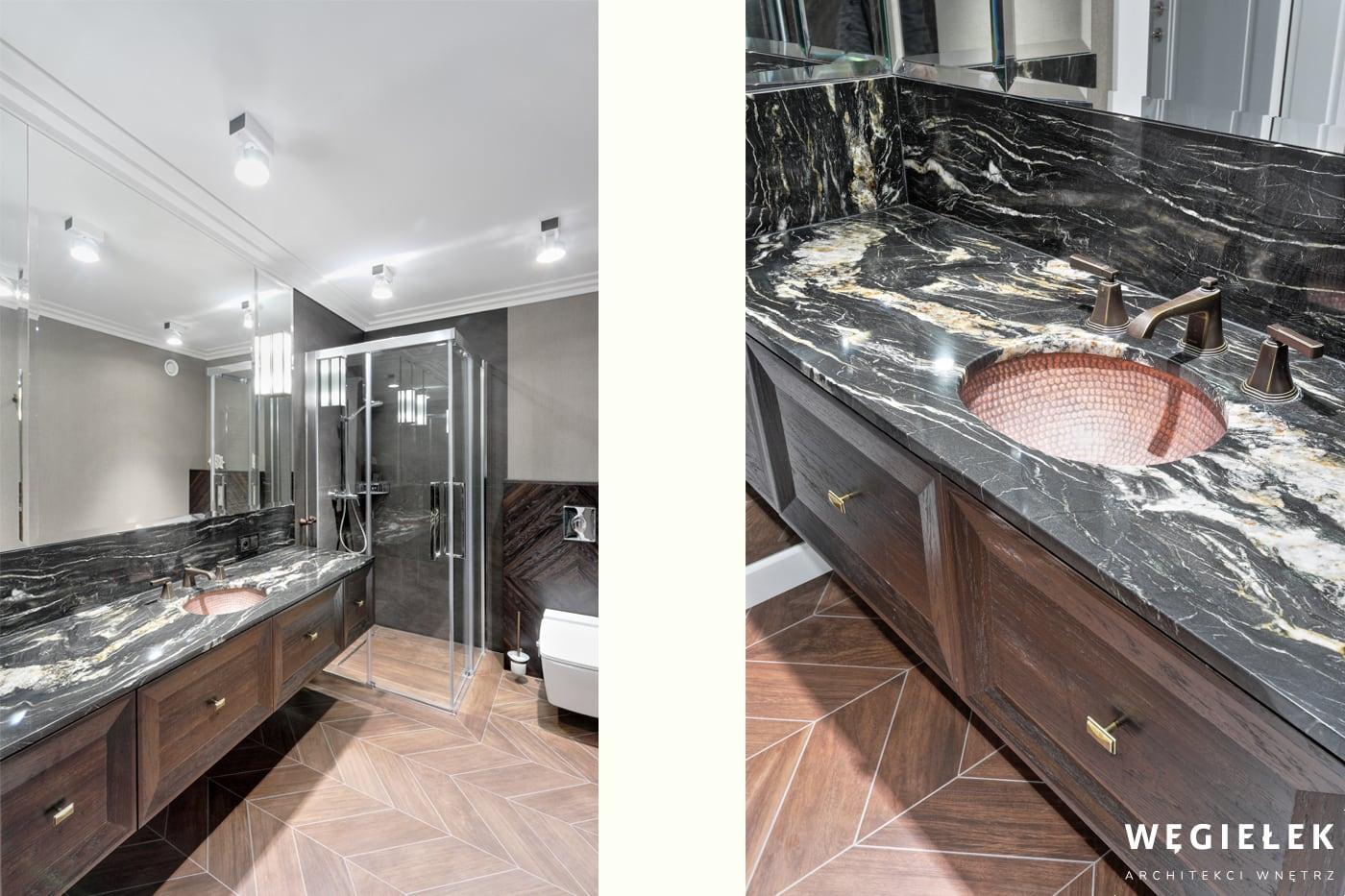 Architekci wnętrz domów prezentują łazienkę z marmurowym blatem o ciekawym wzorze. Podłoga przypomina klasyczny parkiet ułożony w jodełkę. Do tego biały sufit.