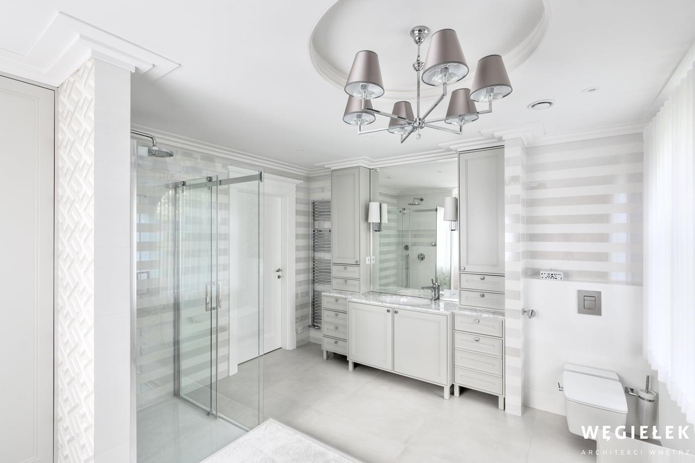 Tę łazienkę w bieli zaprojektowali architekci wnętrz domów z wyczuciem aktualnych trendów. Stanowi ona ciekawe połączenie różnych geometrycznych wzorów.